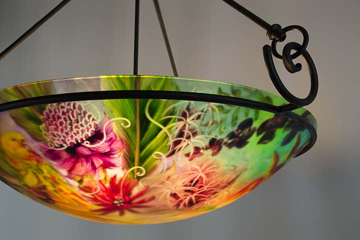 A beautifully painted yellow parrot perches by tropical flowers in this exquisite 24 inch hand painted glass chandelier by artist Jenny Floravita a true work of art.