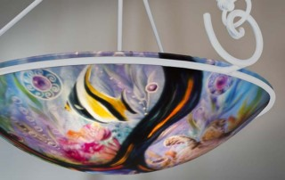 Turtles also known as Honu in Hawaiian and tropical fish swim in a sunlit filled coral reef sea surrounded by volcanic rock in this exquisite 24 inch hand painted glass chandelier by artist Jenny Floravita a true work of art.